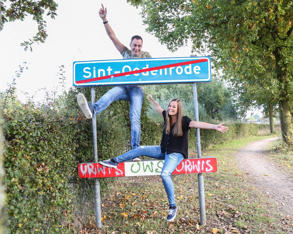 Bram & Manon sitting on the End of Sint-Oedenrode sign