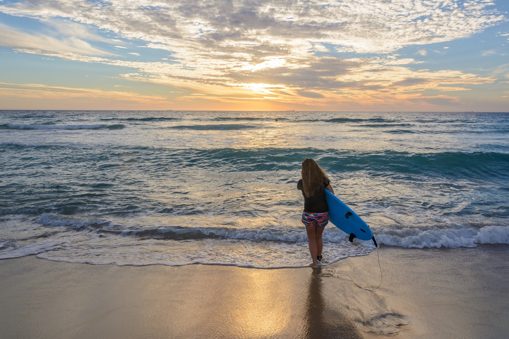 Manon walking into the ocean with a surfboard during sunset