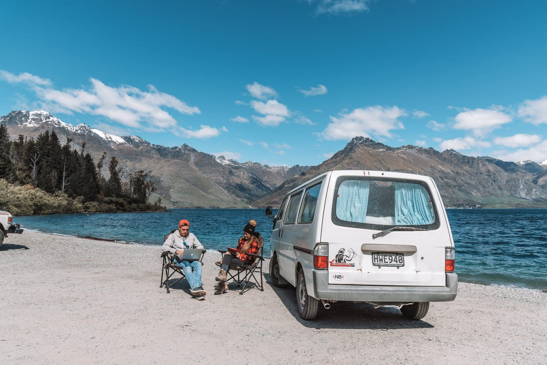 Bram and Manon working on a laptop and iPad besides their campervan next to a lake in Queenstown, New Zealand
