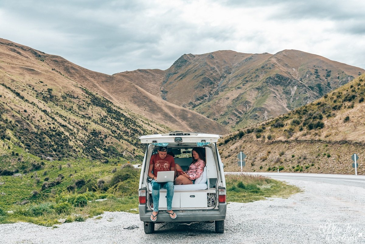 Bram and Manon working inside their campervan at Lindis Pass, New Zealand